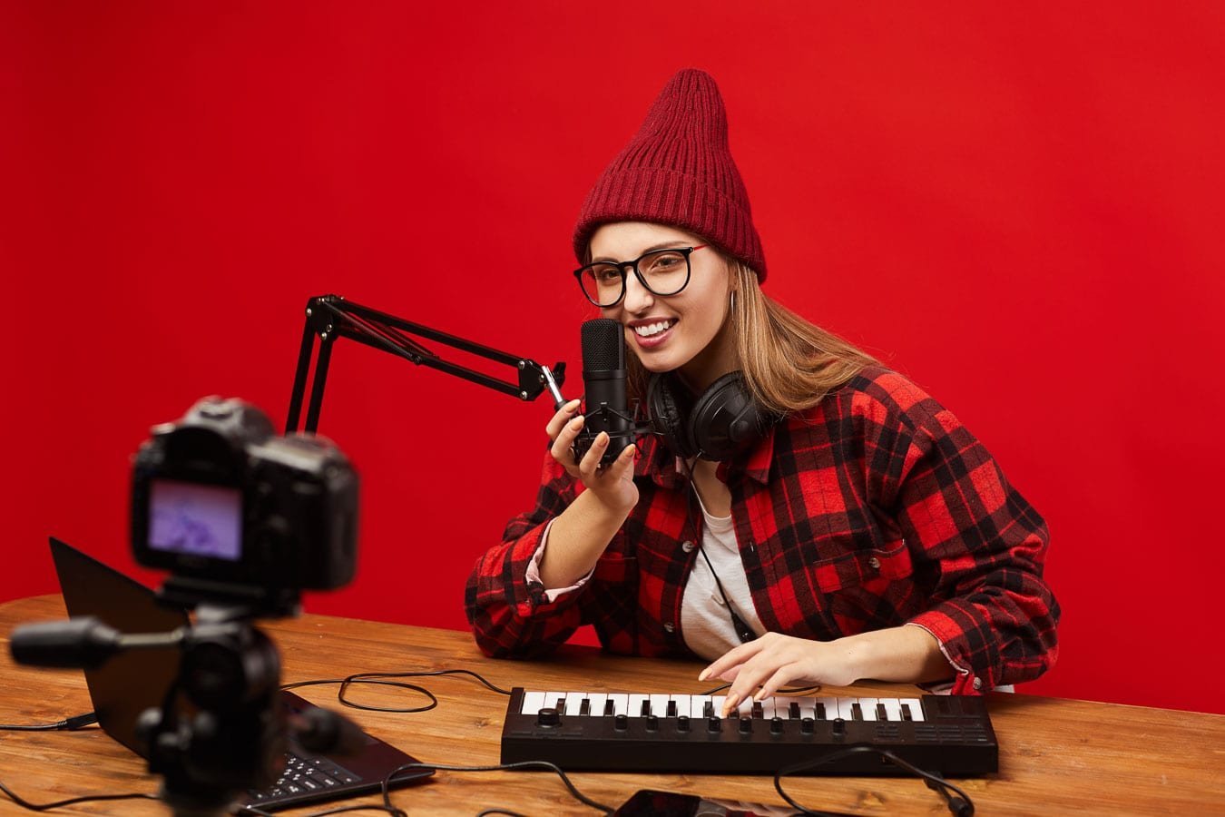 Female playing a keyboard at a desk, in front of a camera