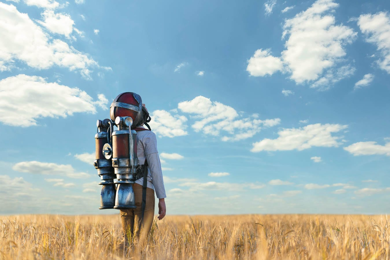boy standing in wheat field wearing a jetpack