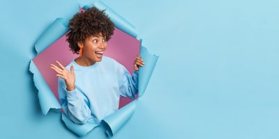 Overjoyed African American woman raises palm and looks gladfully aside as meets someone wears casual jumper poses through paper background in hole expresses positive emotions.