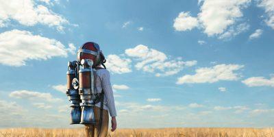 boy standing in wheat field wearing a jetpack